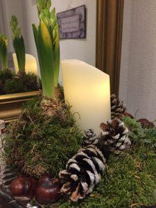 Juledekorationen fra siden med hyacintløgene, der er pakket ind i mos og viklet med sølvtråd