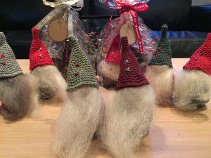 Søde, hjemmehæklede nisser i cellofan med julebånd og træskilt
