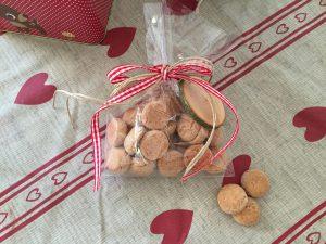 Pebernødder i en cellofanpose og et fint bånd. Træskiltet kan man skrive en lille julehilsen på